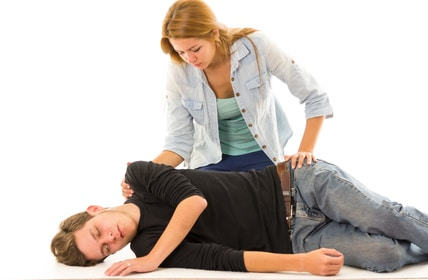 Couple demonstrating first aid techniques with male patient lying in recovery position and female sitting above him.
